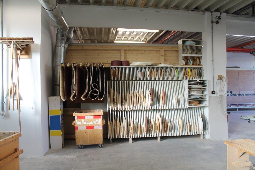 Maschineraum mit Blick auf das Lager für Schleifbänder und Kanten in verschiedenen Farben und Formen